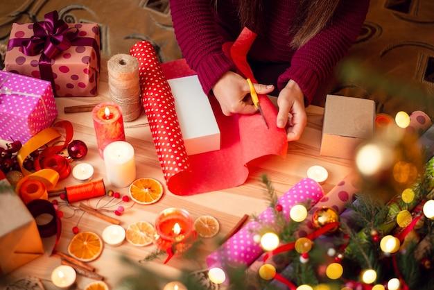 Młoda dziewczyna pakuje prezent w jaskrawoczerwony papier w kropki, przygotowując prezent dla swojej przyjaciółki