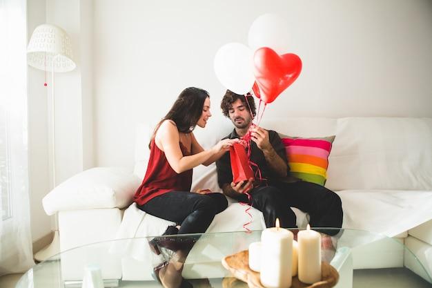 Młoda dziewczyna patrząc na czerwoną torbę, podczas gdy jej chłopak trzyma białe i czerwone balony