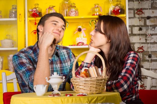 Młoda dziewczyna patrząc na jej uśmiechający się chłopak miło mając randkę w kawiarni.