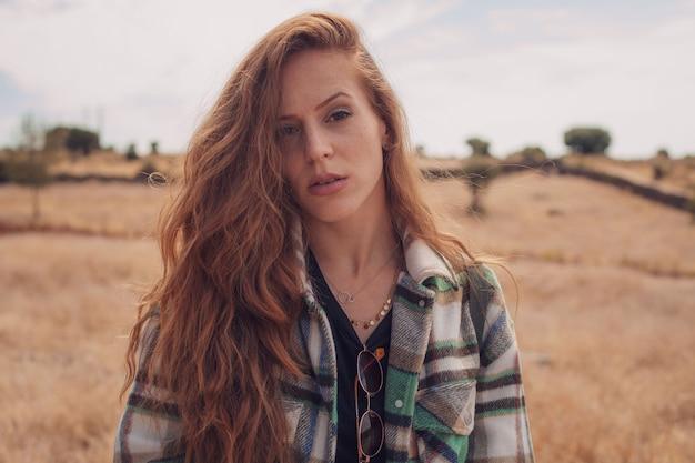 Młoda dziewczyna patrząc w kamerę z polem w jej tle
