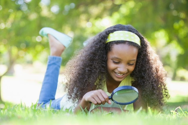 Młoda dziewczyna patrzeje trawy przez powiększać - szkło w parku