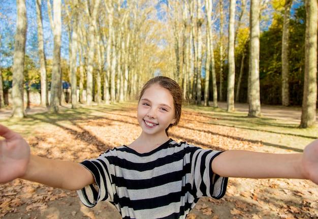 Młoda dziewczyna patrzeje w kamerze w parku