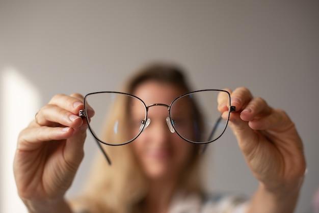 Młoda dziewczyna patrzy przez okulary na wyciągniętych ramionach dziewczyna nieostra