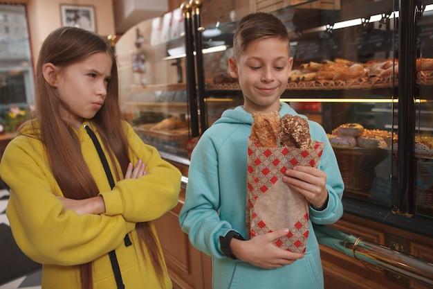 Młoda dziewczyna patrzy ze złością na swojego brata, podczas gdy on cieszy się świeżo upieczonym chlebem