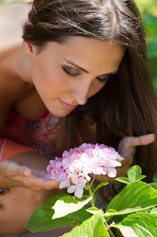 Młoda dziewczyna piękne zapachy kwiatów, przeciwko zielony ogród letni.