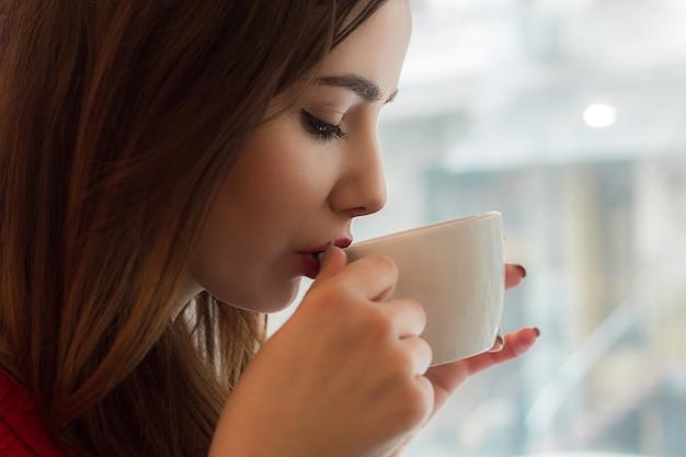 Młoda dziewczyna pije herbatę z małej filiżanki w kawiarni z dużym oknem