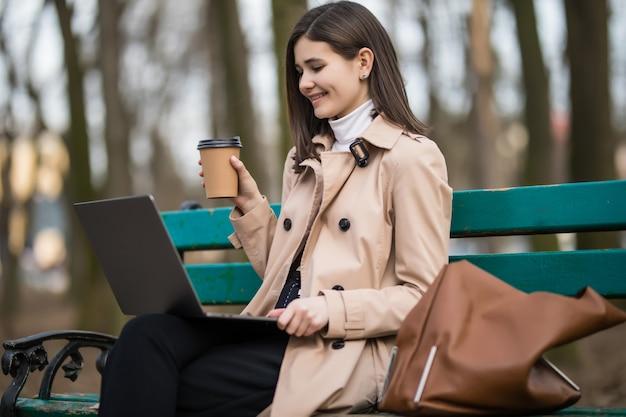Młoda dziewczyna pije kawę i ma połączenie wideo na swoim laptopie na zewnątrz