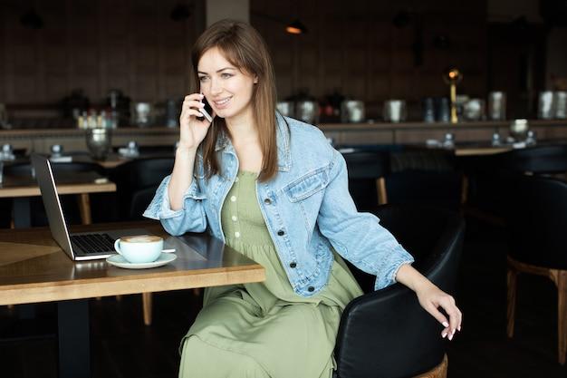 Młoda dziewczyna pije kawę i rozmawia przez telefon