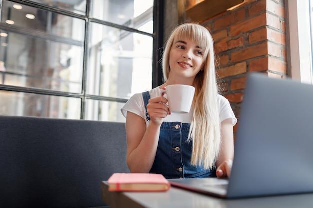 Młoda dziewczyna pije kawę i używa telefon komórkowego w kawiarni. zakupy online