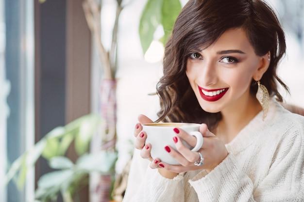 Młoda dziewczyna pije kawę w modnej kawiarni