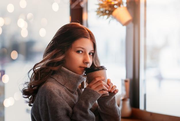Młoda dziewczyna pije kawę z papierowego kubka w miejskiej kawiarni