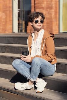 Młoda dziewczyna pije kawowego obsiadanie na schodkach