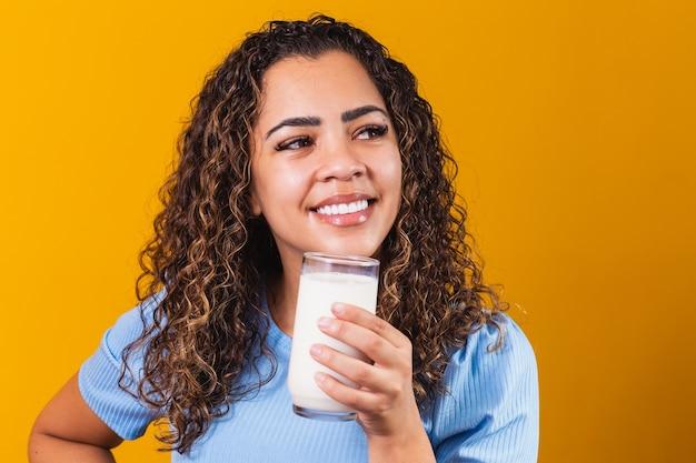 Młoda dziewczyna pije szklankę mleka na tle z miejsca na tekst.