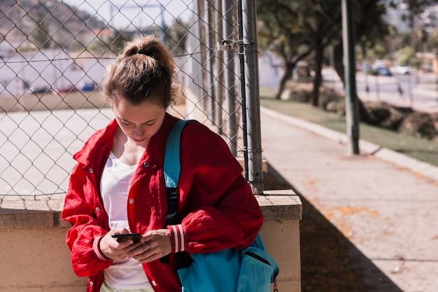 Młoda dziewczyna pisać na maszynie tekst przy smartphone