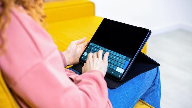 Młoda dziewczyna pisze na swoim tablecie na kanapie. miejsce na tekst. pracować w domu