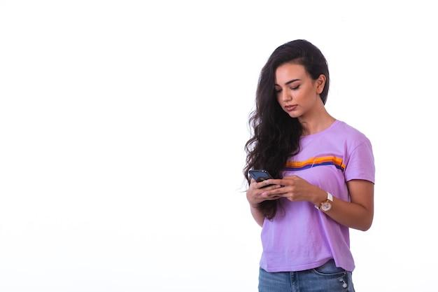 Młoda dziewczyna pisze wiadomości lub prowadzi rozmowę wideo.