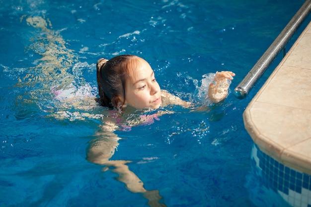 Młoda dziewczyna płynąca do brzegu basenu