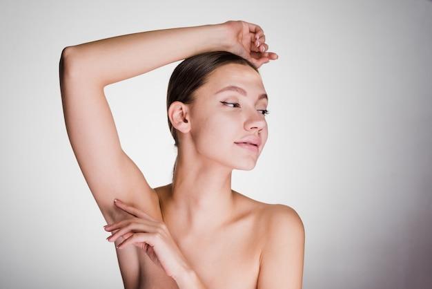 Młoda dziewczyna po prysznicu pokazuje swoje pachy bez włosów