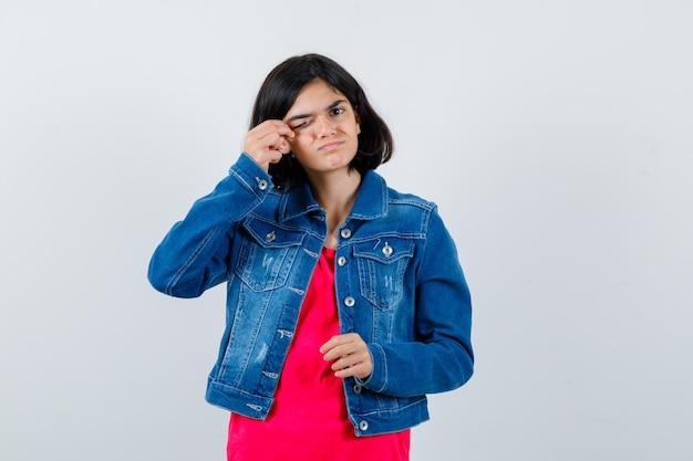 Młoda dziewczyna pociera oko w czerwonej koszulce i dżinsowej kurtce i wygląda na wyczerpaną, widok z przodu.