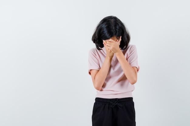 Młoda dziewczyna pociera zakrywającą twarz rękami w różowy t-shirt i czarne spodnie i wygląda na zmęczoną