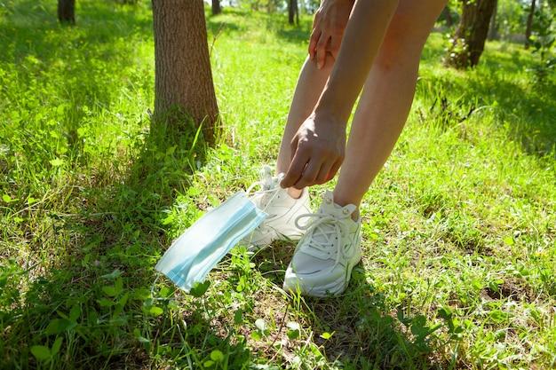 Młoda dziewczyna podnosi maskę w parku