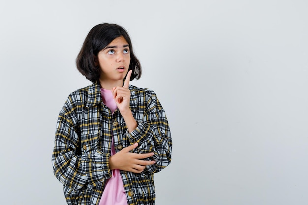 Młoda dziewczyna podnosząc palec wskazujący w geście eureka, trzymając rękę na łokciu w kraciastej koszuli i różowej koszulce i patrząc zamyślony. przedni widok.