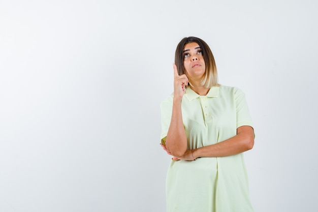 Młoda dziewczyna podnosząc palec wskazujący w geście eureka w t-shirt i patrząc zamyślony, widok z przodu.