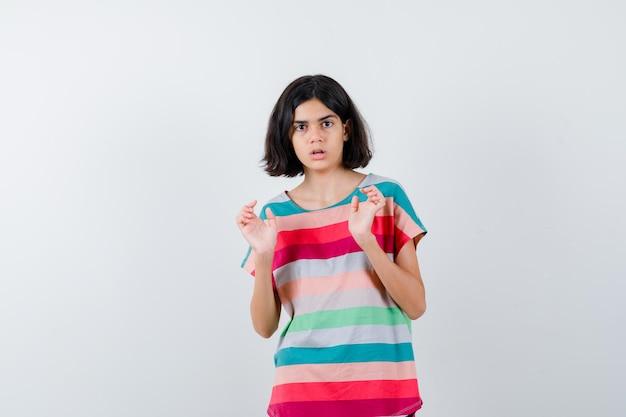 Młoda dziewczyna podnosząc palmy w geście poddania się w kolorowe paski t-shirt i patrząc na zaskoczoną. przedni widok.