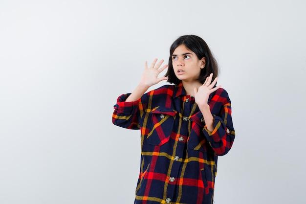 Młoda dziewczyna podnosząca dłonie w geście kapitulacji, odwracająca wzrok w kraciastej koszuli i wyglądająca uroczo. przedni widok.