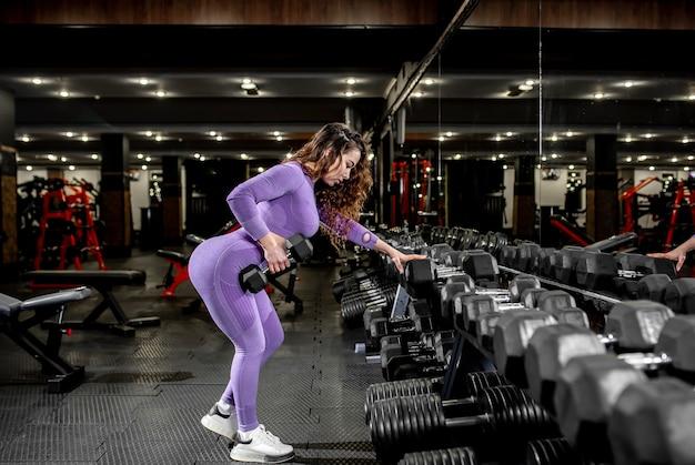 Młoda dziewczyna, podnoszenie ciężarów na siłowni. koncepcja zdrowego stylu życia