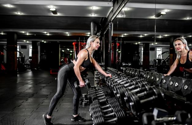 Młoda dziewczyna, podnoszenie ciężarów na siłowni.