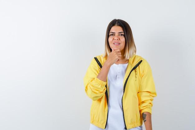 Młoda dziewczyna podpiera podbródek na rękę w białej koszulce, żółtej kurtce i wygląda wesoło, widok z przodu.