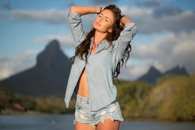Młoda dziewczyna podróżniczka stoi na plaży na tle góry i podziwia piękno morskiego krajobrazu. młoda dziewczyna uwielbia dzikie życie, podróże, wolność.