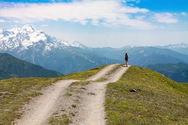 Młoda dziewczyna podróżnik idzie drogą wśród wysokich ośnieżonych szczytów na horyzoncie z miejsca na kopię