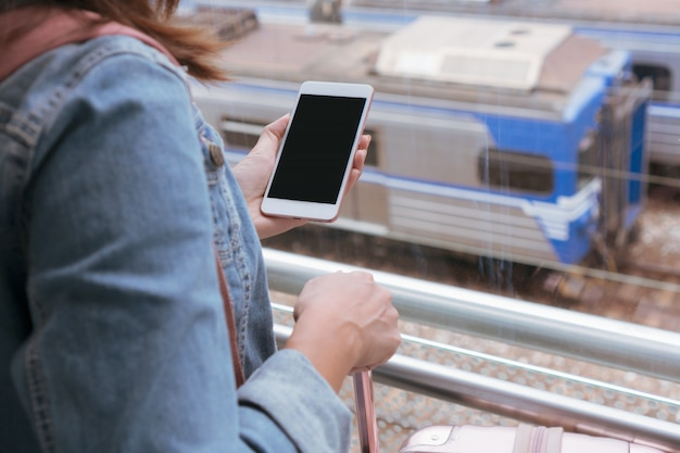 Młoda dziewczyna podróżnik w dżinsowej kurtce z inteligentnym telefonem, różową torbą i bagażem czeka na pociąg na peronie, miejsca kopiowania, podróży lub transportu