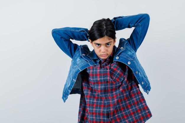 Młoda dziewczyna podwija włosy w kraciastą koszulę i dżinsową kurtkę i wygląda ładnie.