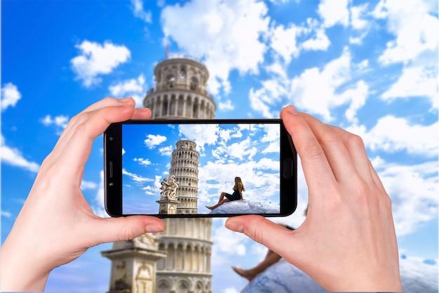 Młoda dziewczyna podziwia krzywą wieżę we włoszech. zdjęcie zrobione telefonem