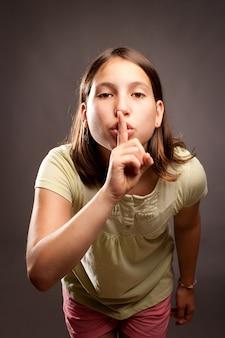 Młoda dziewczyna pokazano gest ciszy na szaro