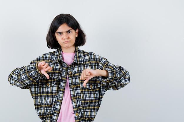Młoda dziewczyna pokazując kciuk w dół obiema rękami w kraciastej koszuli i różowej koszulce i patrząc niezadowolony, widok z przodu.