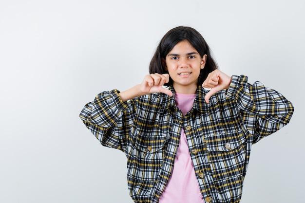 Młoda dziewczyna pokazująca kciuki w dół obiema rękami w kraciastej koszuli i różowej koszulce i wyglądająca na niezadowoloną