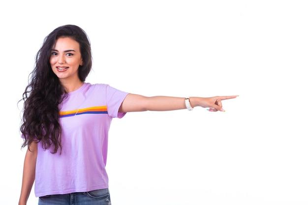 Młoda dziewczyna pokazująca kierunek w prawo ściśle