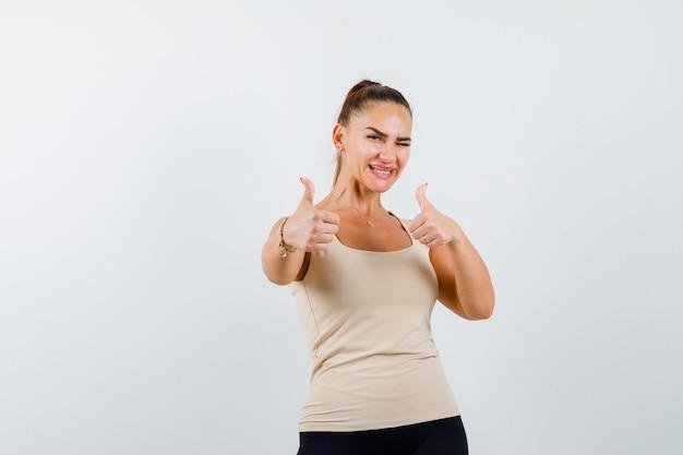 Młoda dziewczyna pokazująca podwójne kciuki w górę, mrugająca w beżowym topie, czarnych spodniach i wyglądająca na pewną siebie. przedni widok.