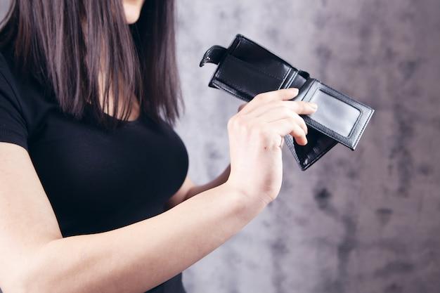 Młoda dziewczyna pokazująca pusty portfel