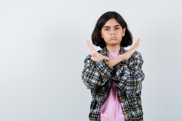 Młoda dziewczyna pokazująca znak x lub gest ograniczenia w kraciastej koszuli i różowej koszulce i wyglądająca poważnie