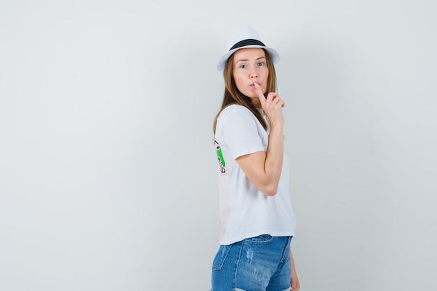 Młoda dziewczyna pokazuje gest ciszy w kapeluszu szorty biały t-shirt i patrząc ostrożnie