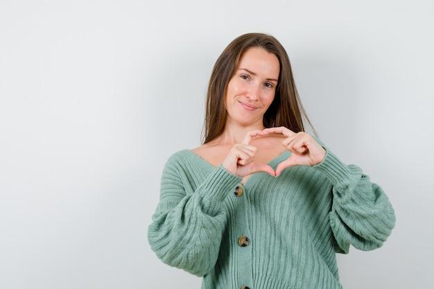 Młoda dziewczyna pokazuje gest miłości rękami w dzianinie i wygląda uroczo. przedni widok.