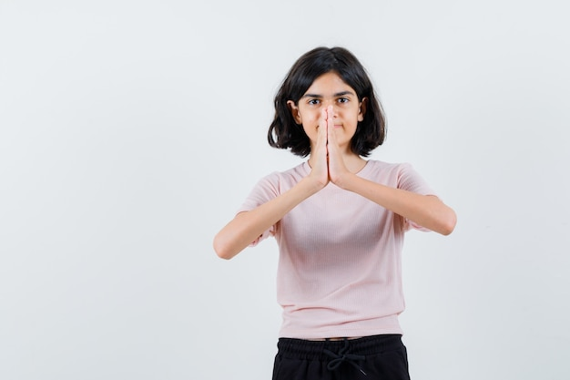 Młoda dziewczyna pokazuje gest namaste w różowej koszulce i czarnych spodniach i wygląda szczęśliwy