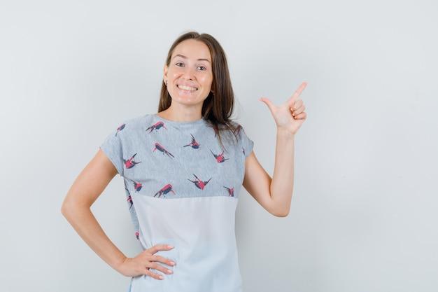 Młoda dziewczyna pokazuje gest pistoletu w koszulce i wygląda szczęśliwy, widok z przodu.