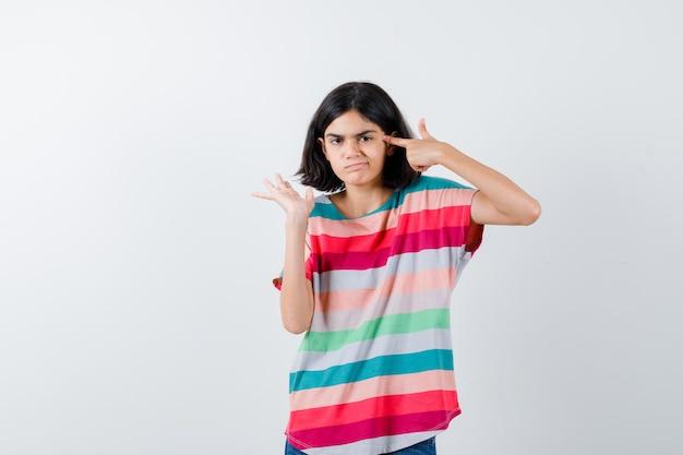 Młoda dziewczyna pokazuje gest pistoletu w pobliżu głowy, rozciągając lewą rękę w kolorowe paski t-shirt i patrząc niezadowolony, widok z przodu.