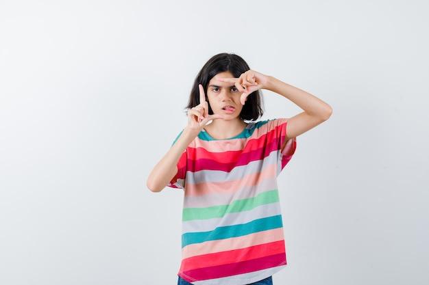Młoda dziewczyna pokazuje gest ramki, wystaje język w kolorowe paski t-shirt i wygląda ładnie, widok z przodu.